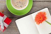 Blank notepad, gift box, coffee cup and orange gerbera flower on wooden table background