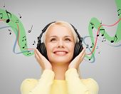 music and technology concept - smiling young woman listening to music with headphones