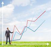 business, development and people concept - smiling man holding graph line over chart background