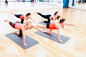fitness, sport, training, gym and lifestyle concept - group of smiling women stretching on mats in t