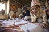 KATHMANDU, NEPAL - DEC 9, 2013: Unknown children doing homework at Jagadguru School. School establis