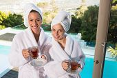 Two smiling young women in bathrobes having tea outdoors