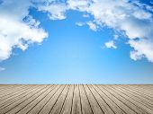 An image of a wooden jetty blue sky background