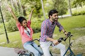 stock photo of tandem bicycle  - Young couple riding bicycle in the park - JPG