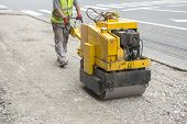 foto of vibrator  - Worker driving Vibration roller compactor on repair pavement - JPG