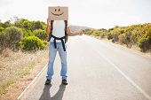 Full length of a man with smiley face hitchhiking on countryside road