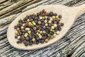 Various peppercorn mix on a old wooden background