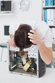 Computer engineer looking at broken device in his office