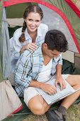 Young couple using laptop in tent on countryside landscape