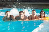 Portrait of cheerful young people playing in the swimming pool