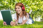 Pretty redhead using her tablet pc while listening to music in the park on a sunny day