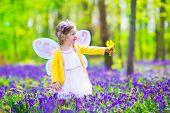 Little Girl In Fairy Costume In Blue Bell Field