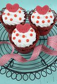 foto of red velvet cake  - Happy Valentine red velvet cupcakes with love messages on vintage baking rack on green teal blue sixties style vintage wood background - JPG
