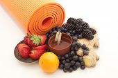 stock photo of yoga mat  - Bright orange yoga mat with ginger tea in a distinctive cup surrounded by bright berries ginger root and citrus - JPG