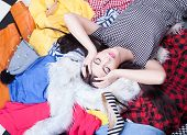 Nothing to wear concept, young attractive woman lying down on a pile of clothes