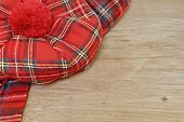 image of headgear  - Traditional Scottish Red Tartan Bonnet and Scarf Men headgear and neckwear on Grunge Timber Board - JPG