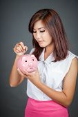 Beautiful Asian Girl Put A Coin To Pink Pig Money Box