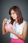 Beautiful Asian Girl Put A Bill To Pink Pig Money Box