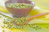 stock photo of sweetpea  - dry green peas in bowl and on a table - JPG