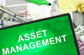 stock photo of asset  - Tablet with words asset management with dollars and euro - JPG