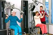 picture of chest  - Two Healthy Old Women Exercising Using Chest Press Equipment at the Fitness Gym with Young Male Instructor - JPG