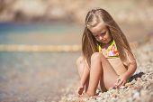 Little girl on the beach near the sea.
