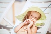 Little girl sunbathing on a sun lounger
