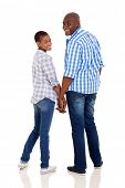 cute young african couple holding hands and looking back isolated on white