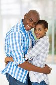 cheerful afro american couple hugging at home