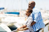 cute young african american couple daydreaming at the harbor