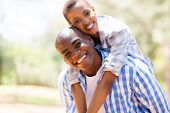pretty african woman enjoying piggyback ride on boyfriend outdoors