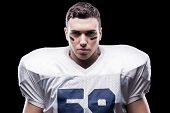 A Real Fighter.  American Football Player Looking At Camera While Standing Against Black Background