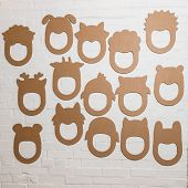 picture of laughable  - Set of cardboard masks on a white brick wall - JPG