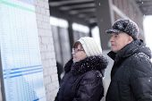 Couple Looks At Train Schedule