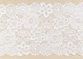 stock photo of lace  - White Ornamental Lace over fabric design for border or background - JPG