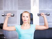 Attractive blond sporty girl doing shoulders training with dumbbell
