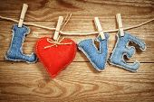 The Love word made of jeans letters with a red textile heart on a rope on a vintage wooden background. St. Valentine's day concept.