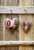 Two  Hearts Hanging Over Rustic Wooden Background. Symbol Of Love.