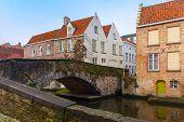 Green canal and bridge in Bruges, Belgium