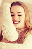 Beautiful caucasian woman is sitting on wooden floor and wearing bright sweater.