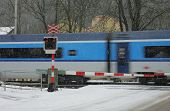 Czech Railway Crossing At Winter With Train In A Snowstorm