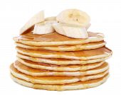 Stack of delicious pancakes with slices of banana and honey on plate isolated on white
