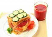 Sandwich with cheese and vegetables on plate near glass of juice isolated on white