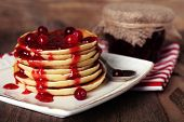 Stack of delicious pancakes with cranberries and jam on plate and napkin on wooden background