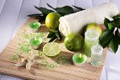 Spa composition with lime, towel and candles on bamboo mat and color wooden background