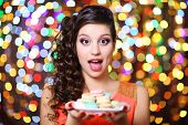 Young beautiful girl with tasty macaroon on bright background