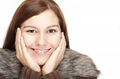 Closeup of a beautiful happy relaxed woman with hands on chin.