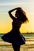 silhouette of young happy woman on sunset sea and beach background