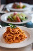Italian spaghetti in tomato sauce in a plate with many other dishes in the background.