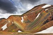 Multicolored rhyolite mountains with the remnants of last year's snow in July. The famous Valley Landmannalaugar in Iceland